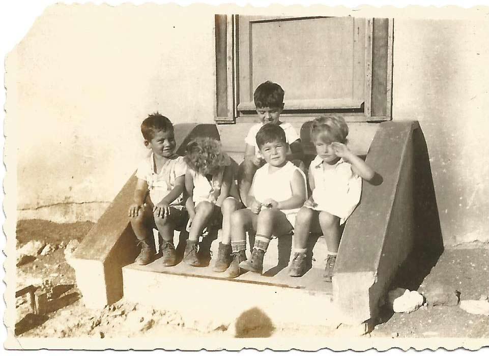 תמונה של ילדים יושבים על מדרגות בית א